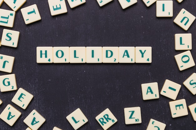 Overhead view of holiday text on scrabble letters over black backdrop Free Photo