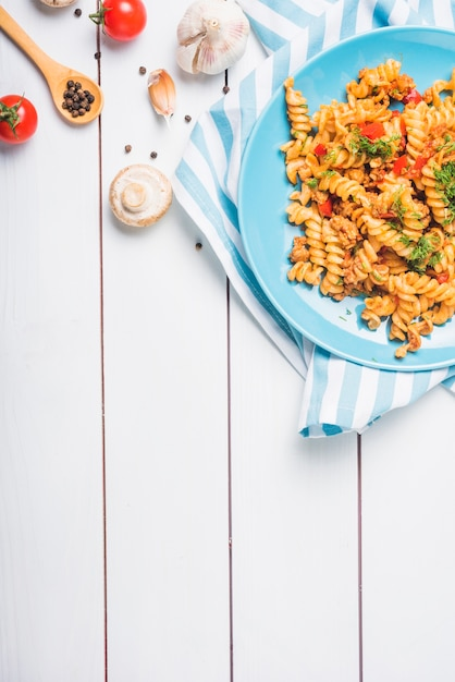 An overhead view of homemade fusilli pasta with ingredients on wooden table Free Photo