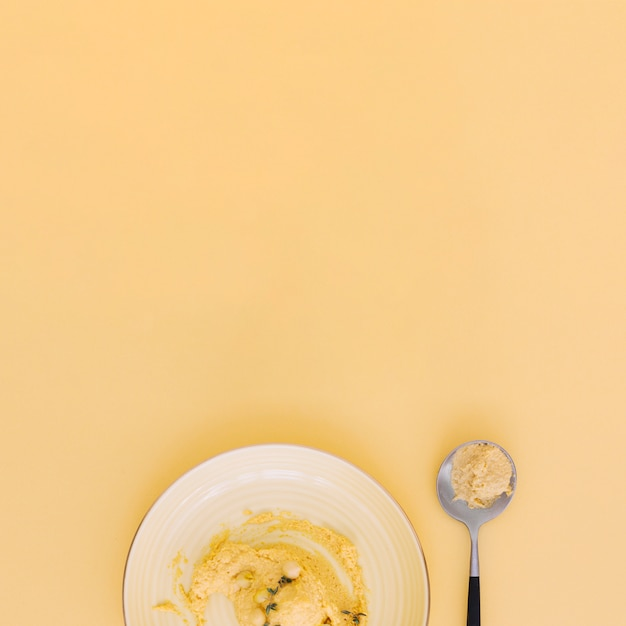 An overhead view of homemade hummus on plate and spoon against beige background Free Photo
