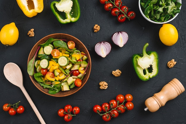 An overhead view of homemade mix vegetable with ingredients on black kitchen worktop Free Photo
