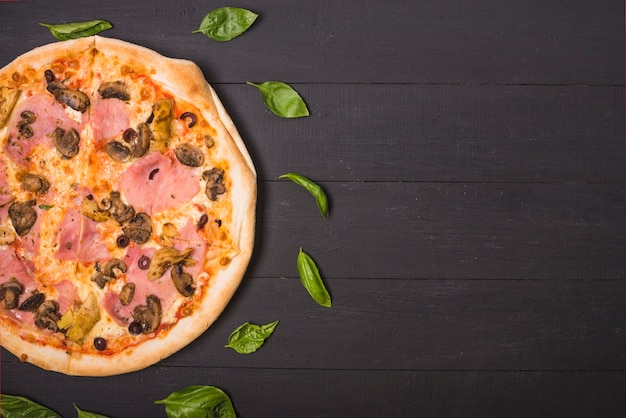 An overhead view of homemade pizza decorated with basil leaves on wooden plank Free Photo