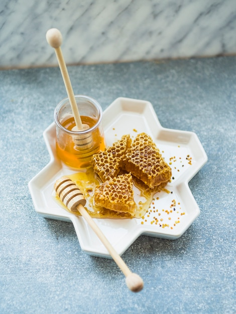 An overhead view of honeycomb pieces and pollen bees on tray Free Photo
