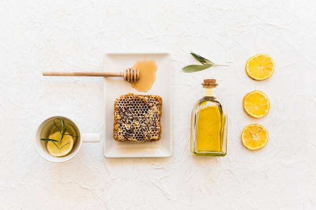 Overhead view of honeycomb with olive oil and lemon slice on white wallpaper Free Photo