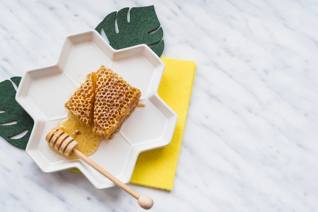 An overhead view of honeycomb with wooden dipper on tray over the white marble Free Photo