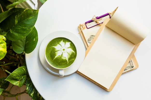 An overhead view of hot matcha green tea latte cup with clipboards on white table Free Photo