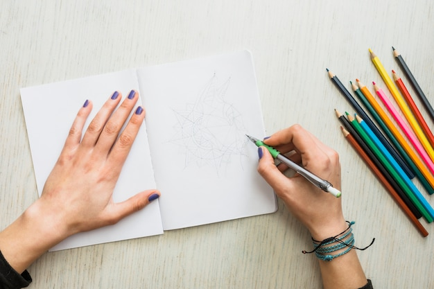 Overhead view of human's hand sketching on white drawing book Free Photo