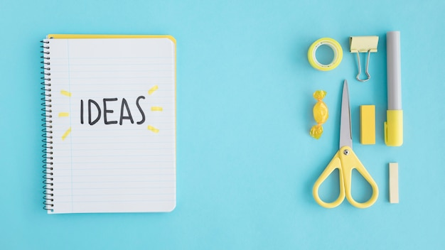 Overhead view of ideas text on notebook with stationary on blue background Free Photo