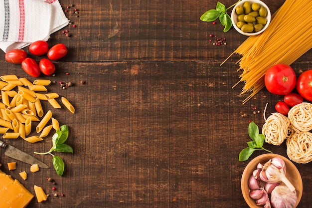 An overhead view of ingredients for making italian pasta on wooden background Free Photo