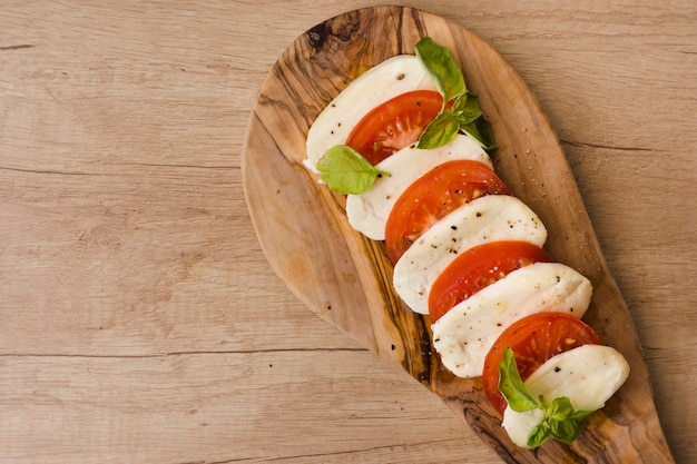 An overhead view of italian caprese salad with slices of mozzarella cheese; basil and tomatoes on serving board Free Photo