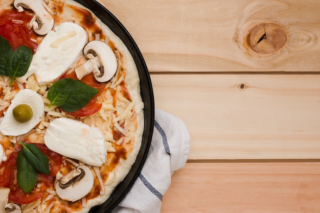 An overhead view of italian pizza on wooden backdrop Free Photo