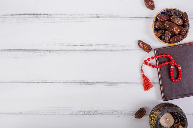 An overhead view of juicy dates; lighted candle; red prayer beads on diary over white desk Free Photo