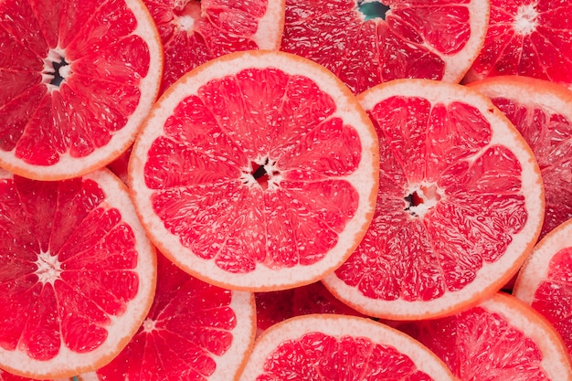 An overhead view of juicy red grapefruits slices background Premium Photo