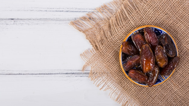 An overhead view of juicy ripe dates bowl on sack cloth over the white desk Free Photo