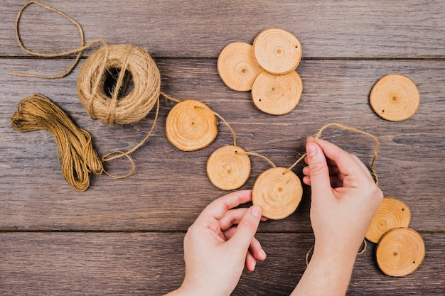 An overhead view of jute spool making garland with tree stump slices on wooden desk Free Photo