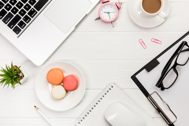 An overhead view of laptop,alarm clock,coffee cup,macaroons,pencil,mouse,spiral notepad on white desk Free Photo