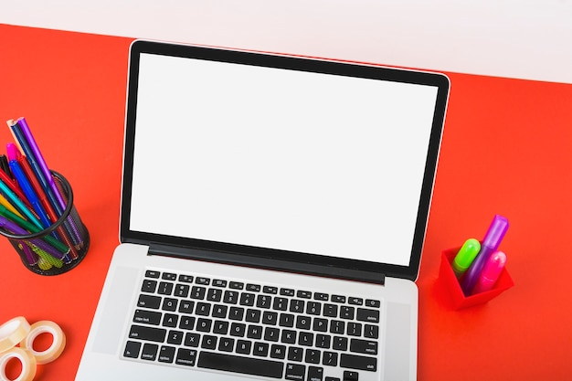 An overhead view of laptop displaying white screen with colorful stationeries on red desk Free Photo