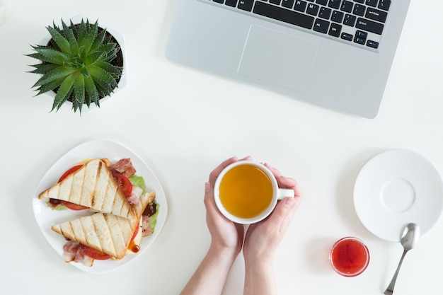 Overhead view of laptop, fresh sandwich, cup of green tea and mobile phone on white desktop table. woman business and breakfast concept, top view and flat lay Premium Photo