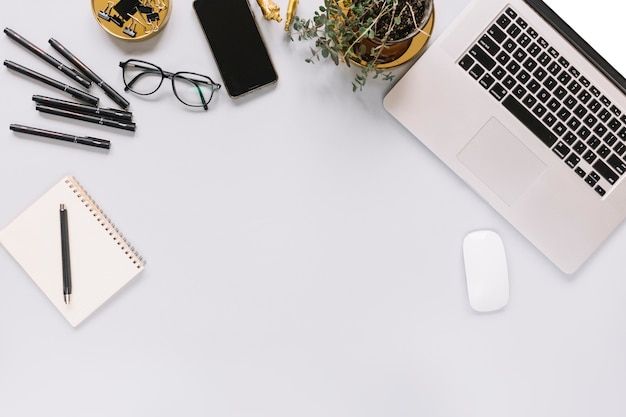 Overhead view of laptop and office stationery on white background Free Photo