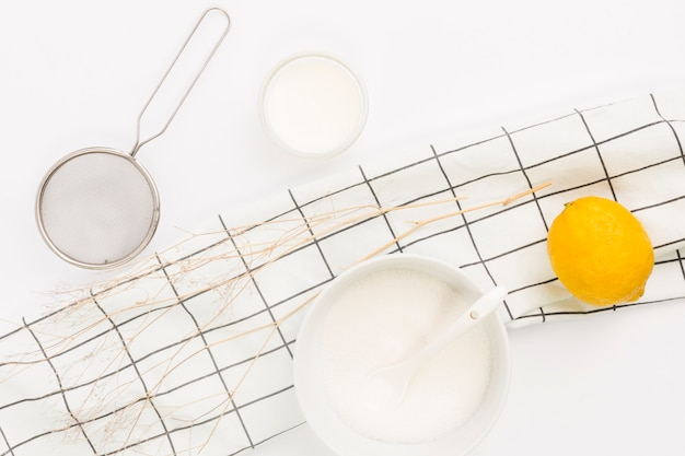 Overhead view of lemon; sugar and kitchen utensil Free Photo