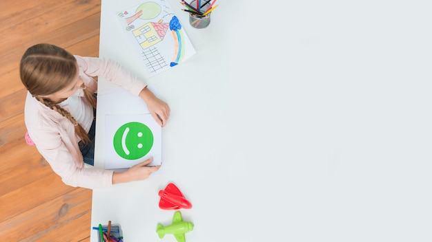 An overhead view of little girl holding happy face emoticons card sitting in the psychologist office Free Photo
