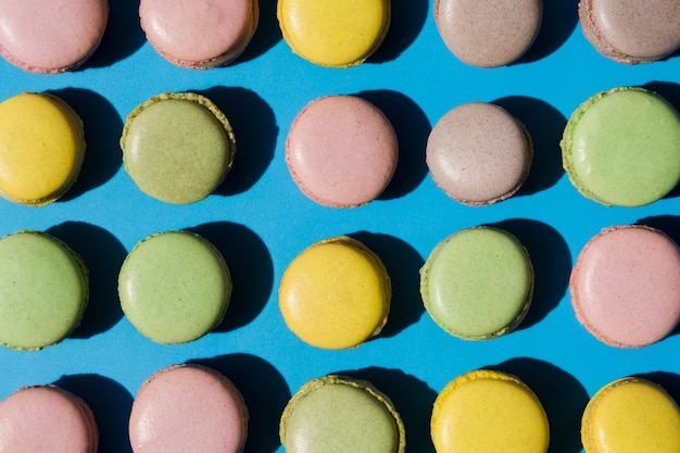 An overhead view of macaroons on blue backdrop Free Photo