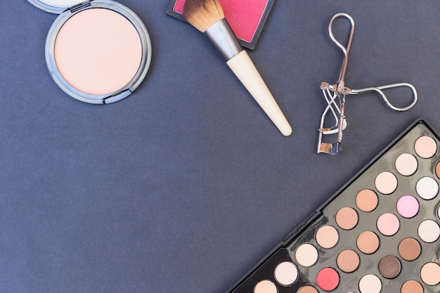 An overhead view of makeup brush; blusher; eyeshadow palette and eyelash curler on blue backdrop Free Photo