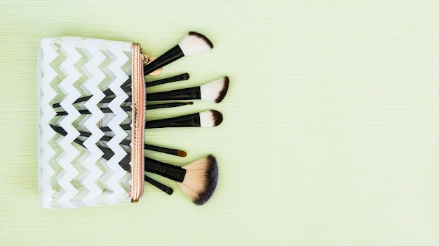 An overhead view of makeup brushes on mint green backdrop Free Photo