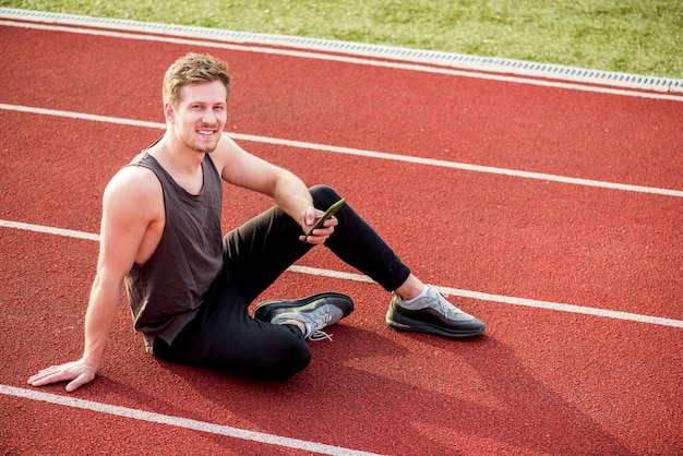 An overhead view of male athlete sitting on red race track holding mobile phone in hand Free Photo