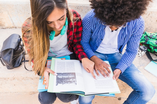 An overhead view of male and female student reading the book Free Photo