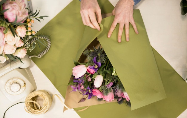 An overhead view of a male florist wrapping the flower bouquet with green paper on table Free Photo