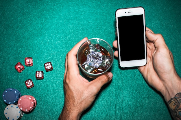Overhead view of man's hand holding cellphone and whisky glass over the poker table Free Photo