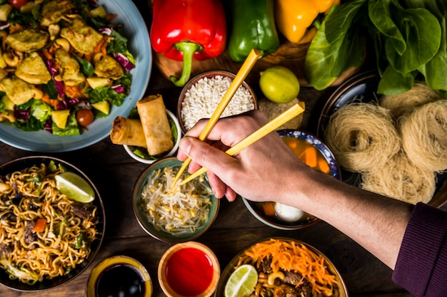 An overhead view of a man's hand holding chopsticks over the delicious thai food Free Photo