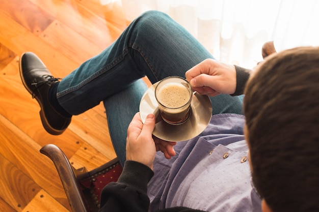 An overhead view of a man sitting on arm chair holding cup of coffee Free Photo