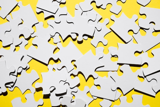 Overhead view of many white jigsaw puzzle pieces Free Photo