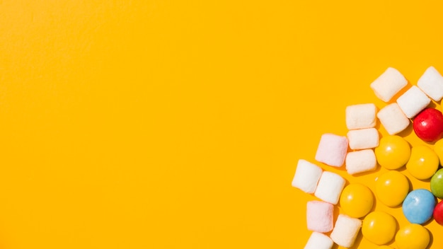An overhead view of marshmallow and colorful candies on yellow background Free Photo