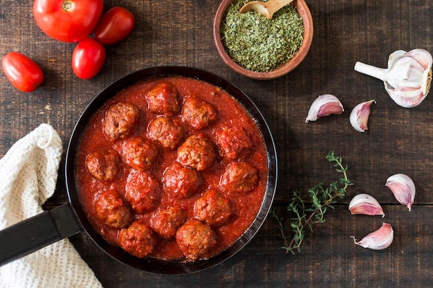 An overhead view of meatballs in sweet and sour tomato sauce with ingredients Free Photo