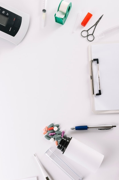 An overhead view of medical equipments with clipboard on white background Free Photo