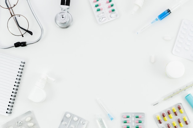 An overhead view of medical pills and equipment's on white background Free Photo
