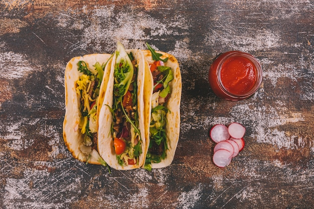 Overhead view of mexican beef tacos with vegetables and tomato sauce over old wooden background Free Photo