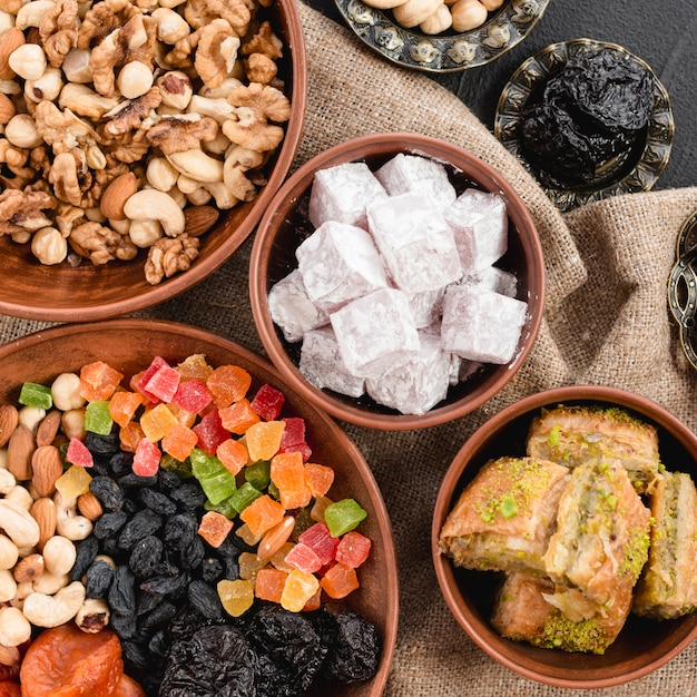 An overhead view of mixed nuts; dried fruits; lukum and baklava in earthen bowl for ramadan Free Photo