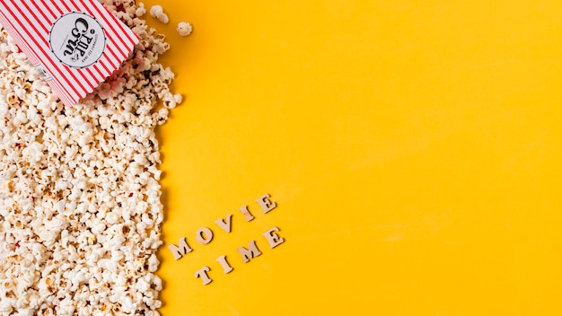 An overhead view of movie time text near the popcorns against yellow background Free Photo