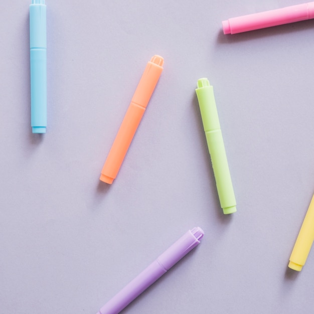 Overhead view of multi colored markers on grey background Free Photo