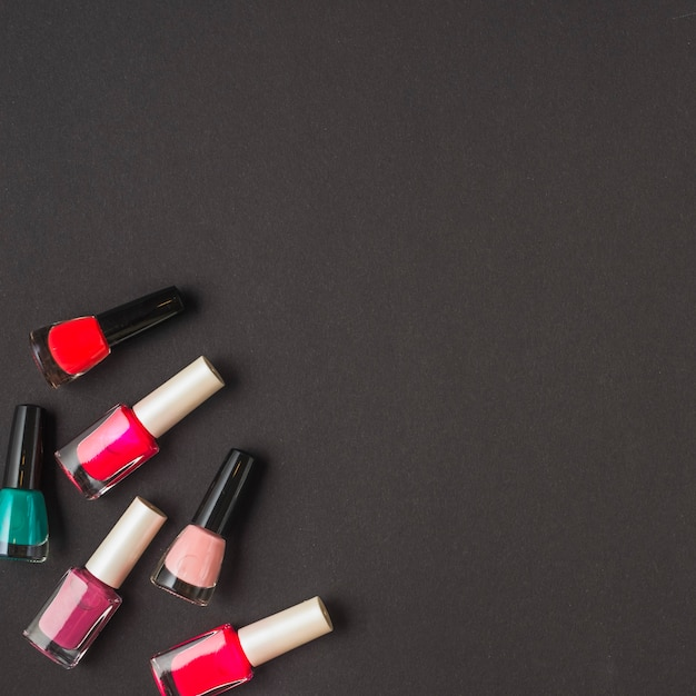 Overhead view of multi colored nail varnish bottles on black surface Free Photo