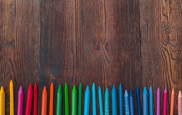 Overhead view of multicolored wax crayons arranged in row at bottom of the background Free Photo