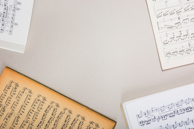 An overhead view of musical note books on white background with space for text Free Photo