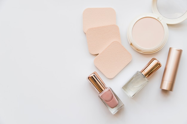 An overhead view of nail polish bottle; lipstick; sponge and compact on white background Free Photo