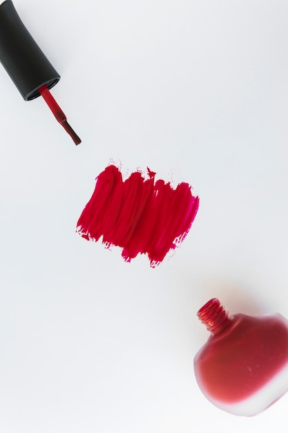An overhead view of nail varnish stroke and bottle on white background Free Photo