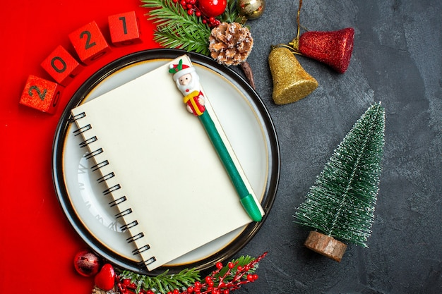 Overhead view of new year background with notebook with pen on dinner plate decoration accessories fir branches and numbers on a red napkin next to christmas tree on a black table Free Photo