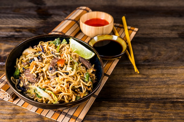 An overhead view of noodles with soya and red chili sauces on place mat over the wooden desk Free Photo