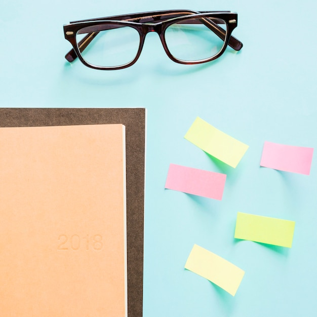 Overhead view of notebook; adhesive notes and spectacles on colored background Free Photo